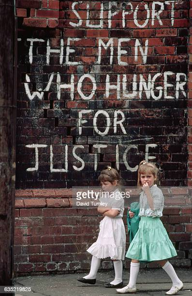 Two Catholic girls walk by a slogan supporting the hunger strikers of the Irish Republican Army and Sinn Fein