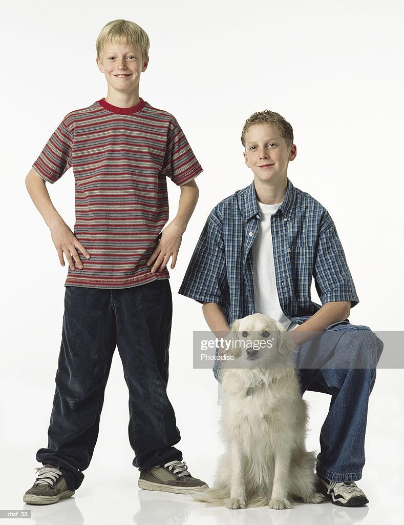 two caucasian blonde brothers with one standing with hands on hips the other kneeling with white retriever mix dog : Foto de stock