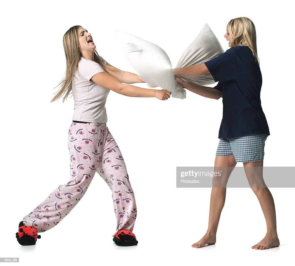 two caucasian blonde female teens dressed in pajamas have a pillow fight : Foto de stock