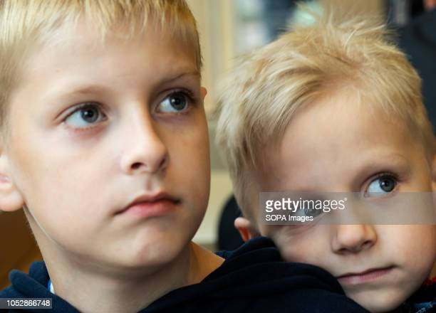 Two Caucasian boys blueeyed blonde brothers are seen together