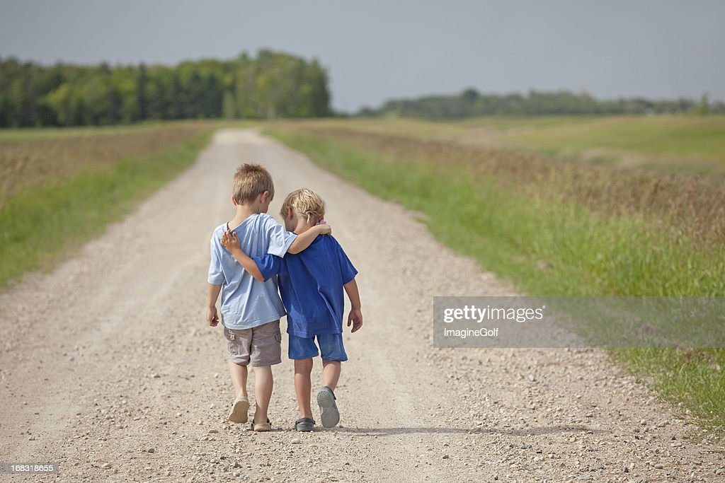 Two Caucasian Boys Walking Down a Country Road : Stock Photo