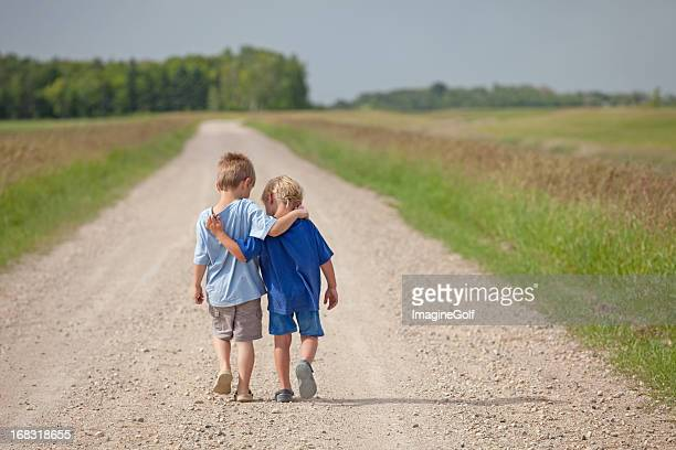 two caucasian boys walking down a country road - arm around stock pictures, royalty-free photos & images