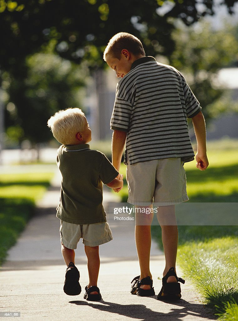Two caucasian brother go for a walk down a sidewalk : Stockfoto