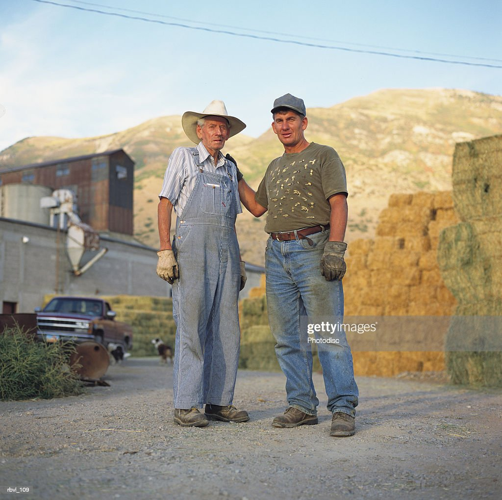 two caucasian farmers dressed for working in the field are standing together in front of bales of hay and a large barn : Foto de stock