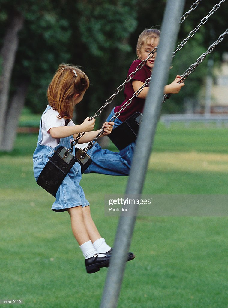 two caucasian female friends play together on the swings : Stockfoto