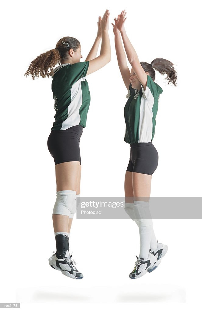 two caucasian female volleyball players from the same team jump in the air and high five each other celebrating a victory : Foto de stock