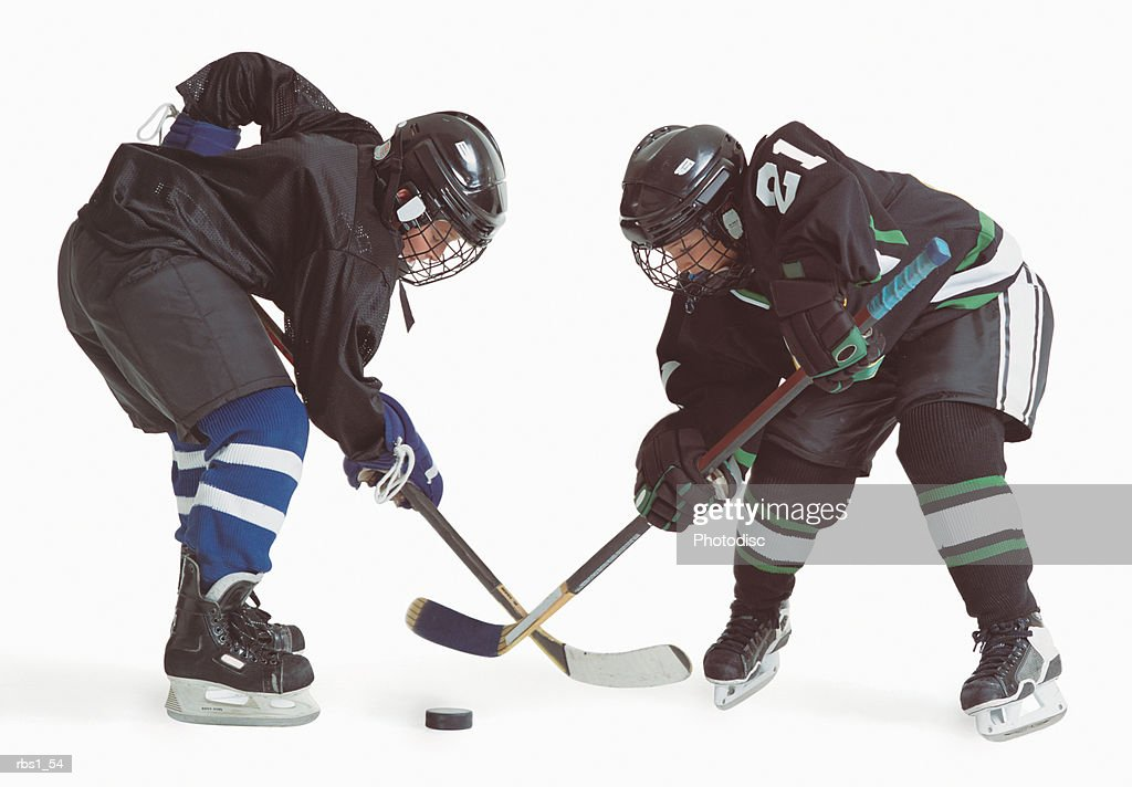 two caucasian hockey players wearing opposing uniforms are holding thier sticks and leaning forward trying to hit the puck : Foto de stock