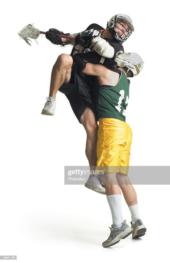 two caucasian male lacrosse players from opposing teams collide as one blocks the other when he jumps in the air : Stockfoto