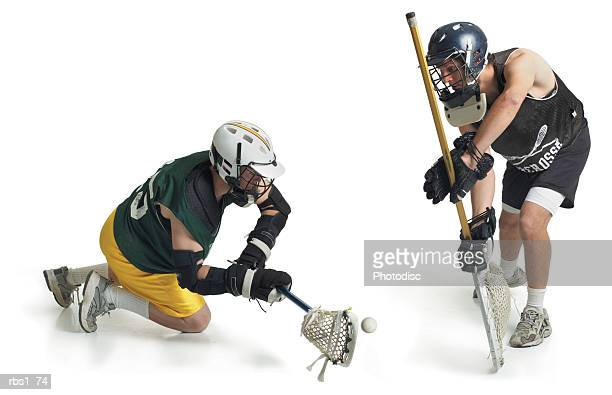 two caucasian male lacrosse players from opposing teams confront each other as one steals a pass from the other