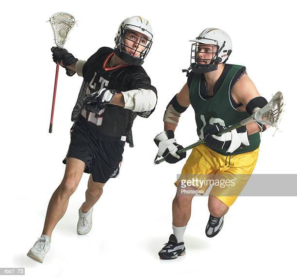 two caucasian male lacrosse players from opposite teams run as the one in the green jersey tries to block the one in black - lacrosse fotografías e imágenes de stock