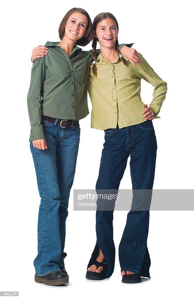 two caucasian teenage girls in a jeans and green shirt puts their arms around each other and smile : Foto de stock