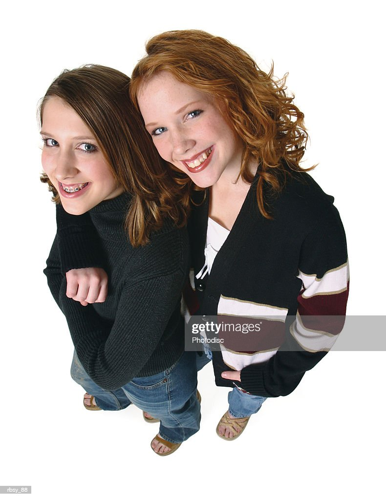 two caucasian teenager girls in jeans and a black sweaters smiles up into the camera : Stock Photo