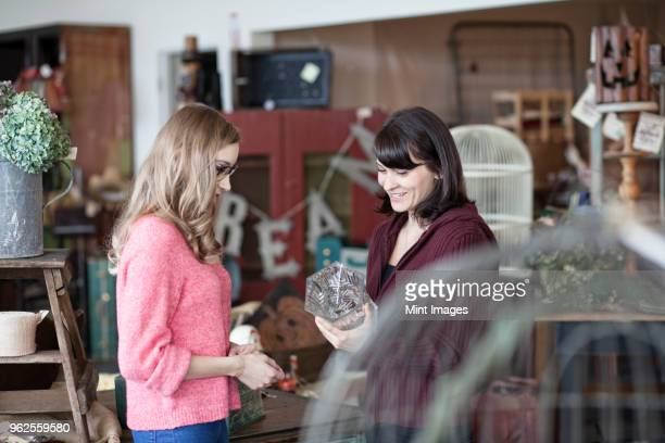 Two Caucasian women shopping in an antique store