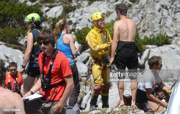 Two cave and mountain rescue experts from Germany shake hands after their descent into the Riesending cave on the Unterberg mountain near...