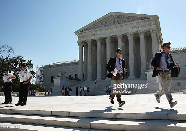 Two CBS interns run with a newly released Supreme Court ruling June 20 2016 in Washington DC The ruling stated that the high court declined to hear...