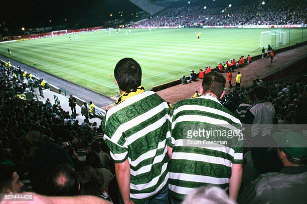 Two Celtic fans get out of their seat to watch the action on the pitch at Celtic's ground Parkhead Celtic have a strong following of mostly Irish...