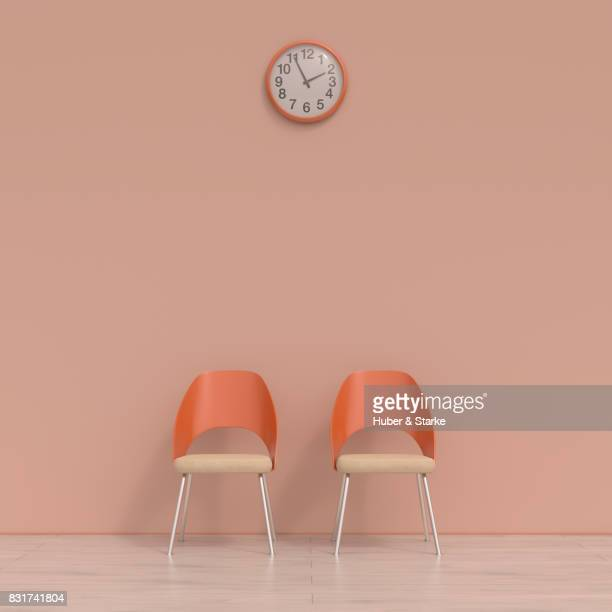 Two chairs and a wall clock in a waiting room