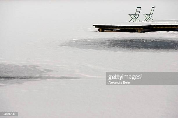 Two chairs are seen on a pontoon at the Wessling lake on December 21 2009 in Wessling Germany Heavy snowfall hit Bavaria
