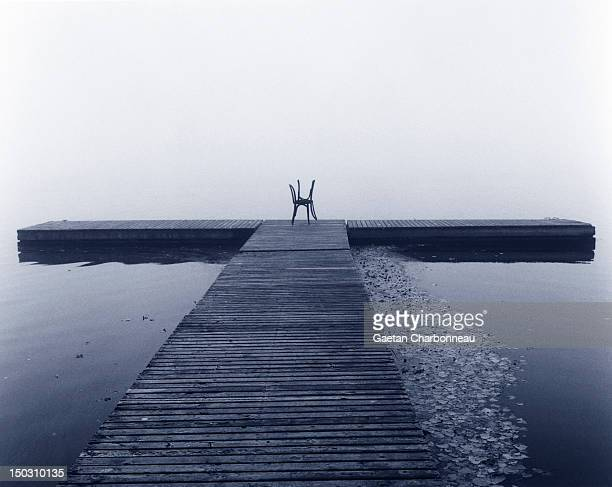 Two chairs at the end of a quay on a foggy day