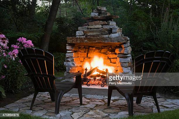 Two chairs in front of outdoor fireplace
