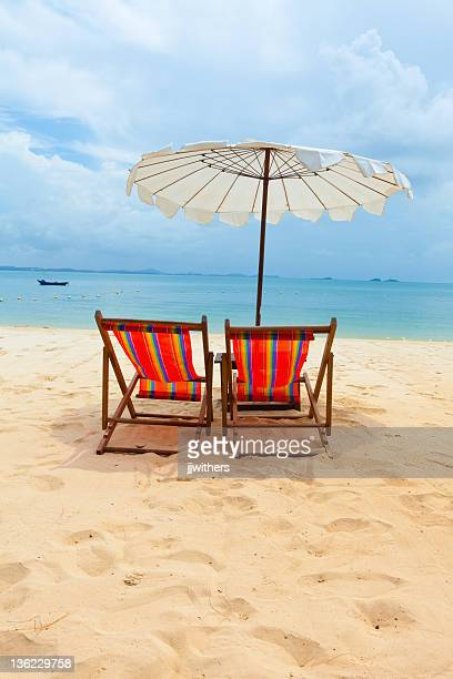 Two chairs in the sand under umbrella on beach
