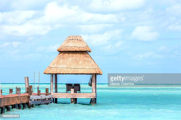 Two chairs on dock under palapa, Cancun, Mexico