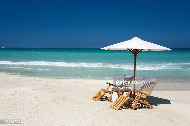 two chairs with umbrella on a beach in florida - outdoor chair stock pictures, royalty-free photos & images