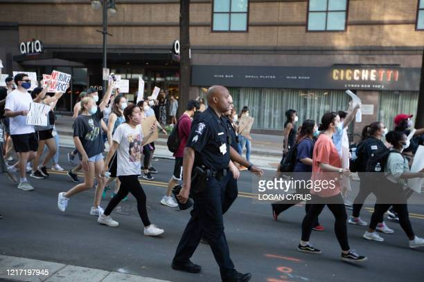Two Charlotte-Mecklenburg police officers march with protestors as they demonstrate for the end of police brutaity during a rally organized by the...
