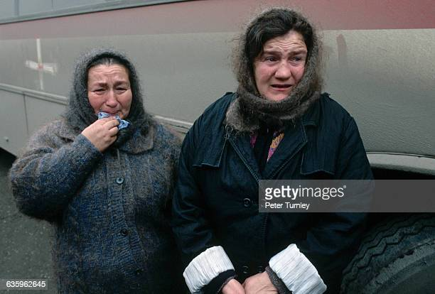 Two Chechen women express their grief with tears after fleeing the war and taking shelter in railroad cars