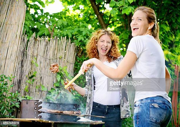 Zwei fröhlich schöne junge Frauen Vorbereitung party-barbecue im Garten