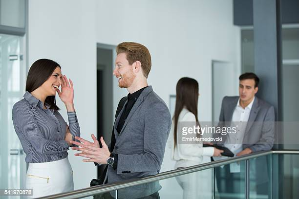 Two cheerful business people talking in office building hallway.