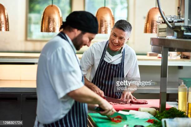 two cheerful chefs working in commercial kitchen - 40 44 years stock pictures, royalty-free photos & images