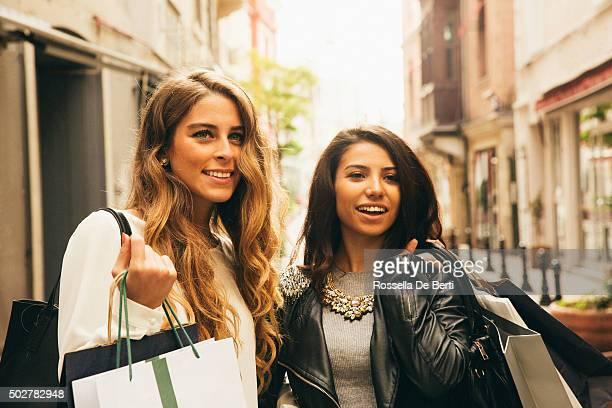 Zwei fröhlich Freunde hängen an und Einkaufsmöglichkeiten