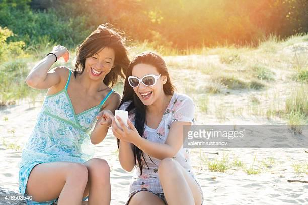 2 つの陽気なご友人とスマートフォンを使用して、ビーチ