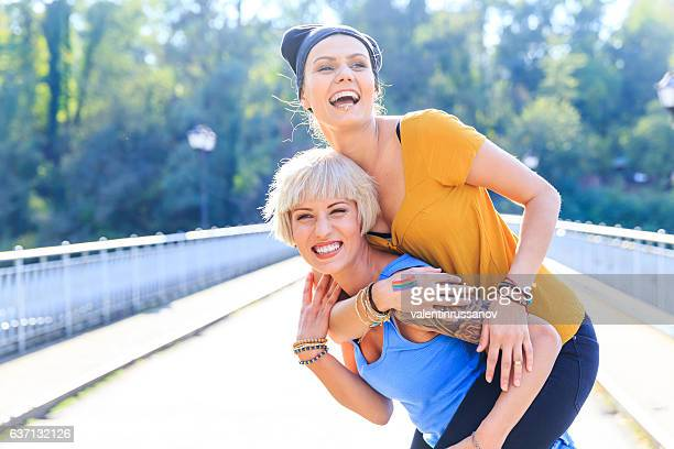 Two cheerful girls having fun in piggyback ride on bridge