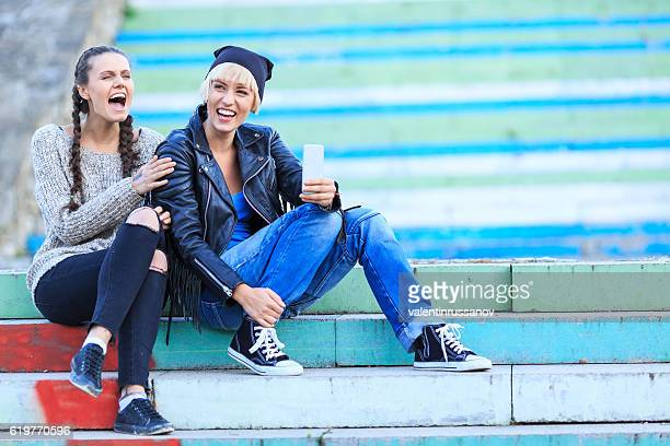 Two cheerful girls sitting on stairs