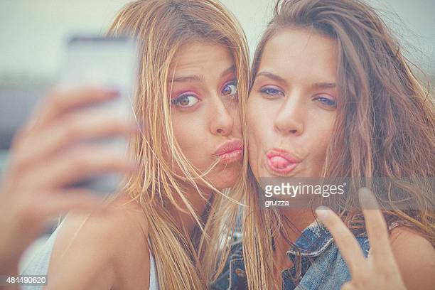 Two cheerful hipster friends taking selfie photos on smart phone