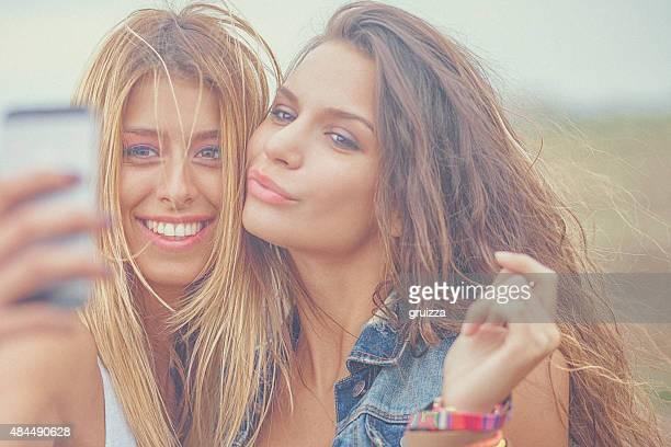 Dois Alegre hipster amigos a tirar uma selfie fotografias no smartphone