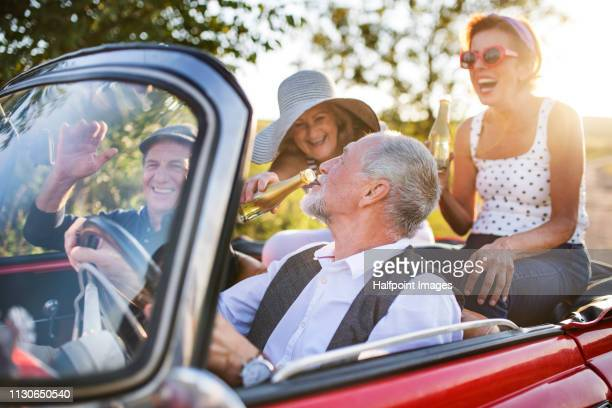 Two cheerful senior couples in cabriolet on a road trip in summer at sunset, having fun.