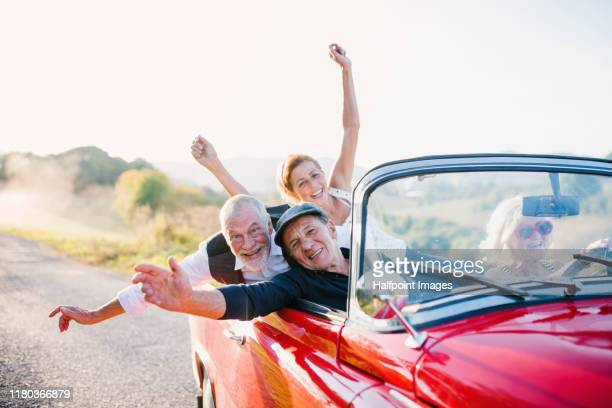 two cheerful senior couples in cabriolet on a road trip in summer at sunset, having fun. - convertible stock pictures, royalty-free photos & images