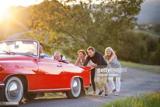 Two cheerful senior couples pushing a broken convertible car up the road trip in summer at sunset.