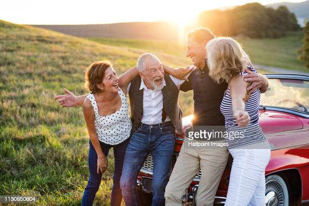 Two cheerful senior couples standing arm in arm by cabriolet on a road trip in summer at sunset.