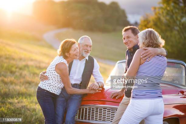 Two cheerful senior couples standing by cabriolet on a road trip in summer at sunset.