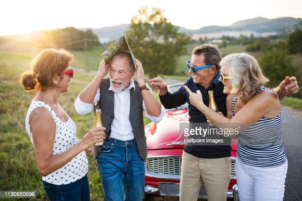 Two cheerful senior couples standing by cabriolet on a road trip in summer at sunset, having fun.