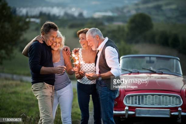 Two cheerful senior couples standing by cabriolet on a road trip in summer at dusk, holding sparkles.