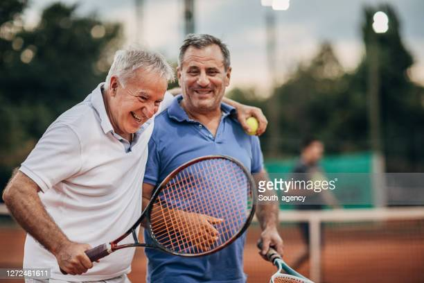 two cheerful senior men talking while walking on the outdoor tennis court - tennis stock pictures, royalty-free photos & images