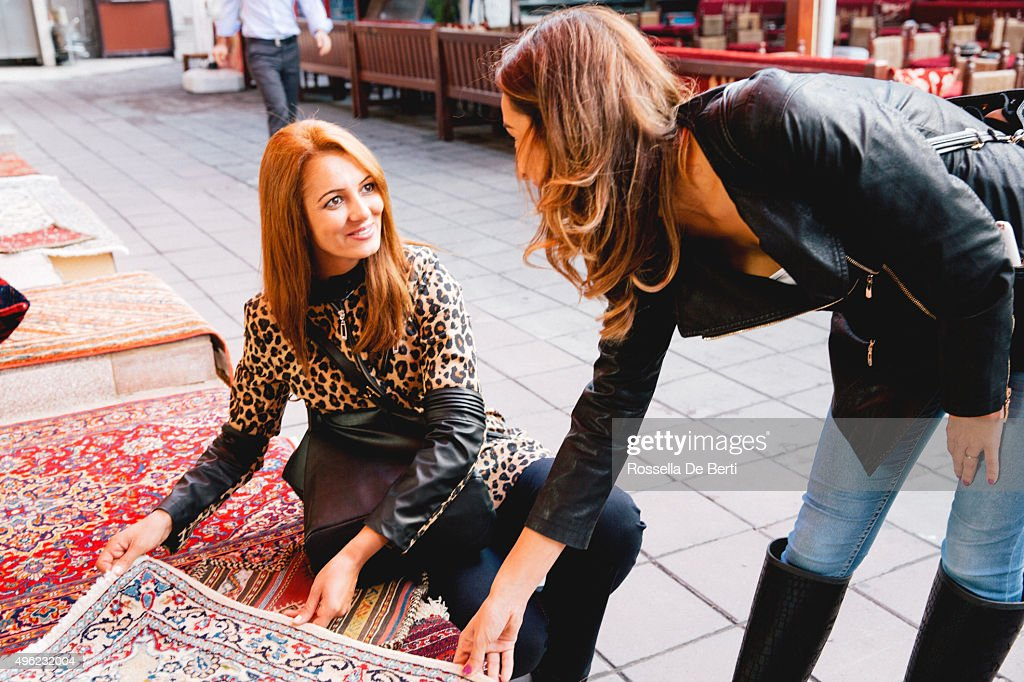 Two Cheerful Women Buying Carpets : Stock Photo