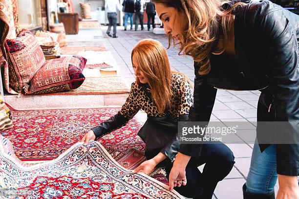 two cheerful women buying carpets - tapijt stockfoto's en -beelden