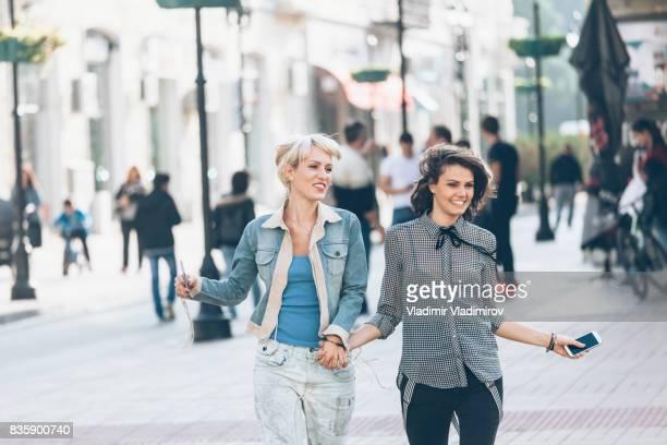dos mujeres jóvenes alegres bailando en la calle y las manos - 22 jump street fotografías e imágenes de stock