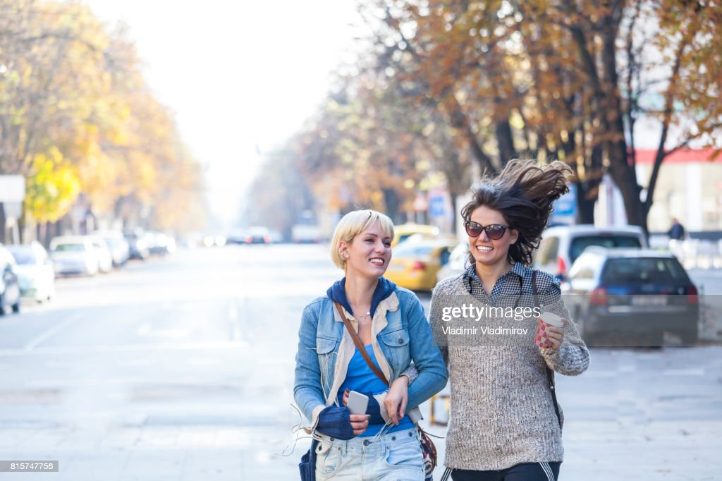 Two cheerful young women walking on street and having fun : Stock Photo